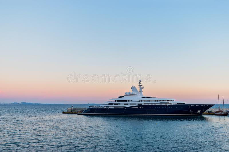 Big luxury super motor yacht at dock of the port. On background of sunset stock photography