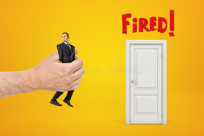 Big male hand bringing tiny businessman to white doorway with red Fired sign on yellow background stock photos