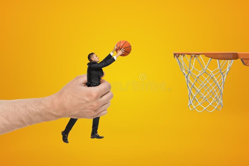 Big male hand holding businessman with basketball ball reaching out to hoop on yellow background. Management and marketing. Games and sports. Sporting goods royalty free stock image