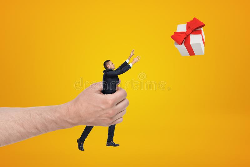 Big male hand holding businessman reaching out to gift box on yellow background royalty free stock photos