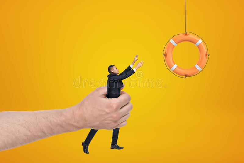 Big male hand holding businessman reaching out to orange boat lifebuoy on yellow background. Management and marketing. Risk and hazard. Life saving royalty free stock image