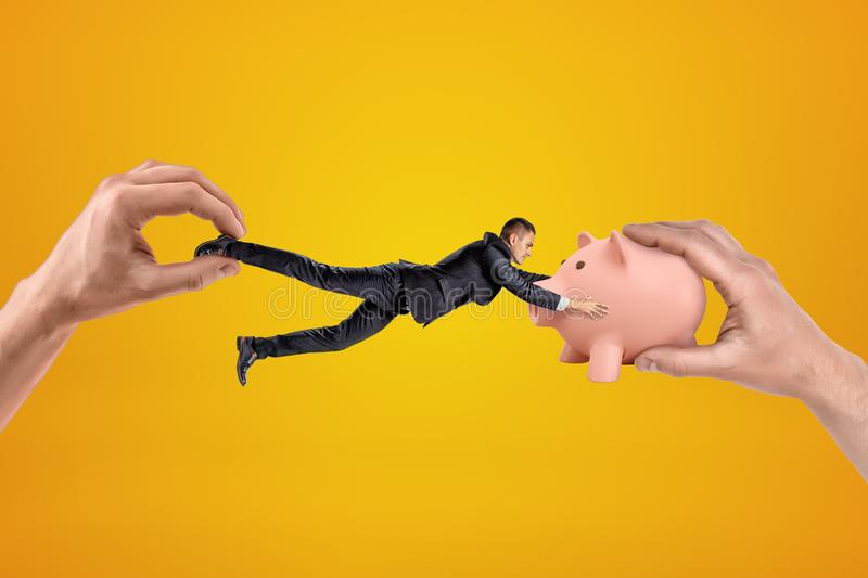 Big male hand holding tiny businessman who is reaching to another big hand holding pink piggy bank on yellow background stock image