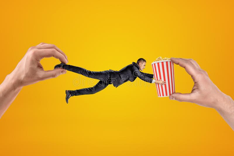 Big male hand holding tiny businessman who is reaching to another big hand holding popcorn bucket on yellow background royalty free stock photography