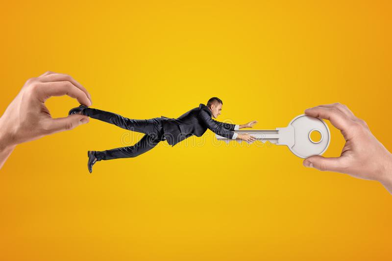 Big male hand holding tiny businessman who is reaching to another big hand holding silver metal key on yellow background stock photo