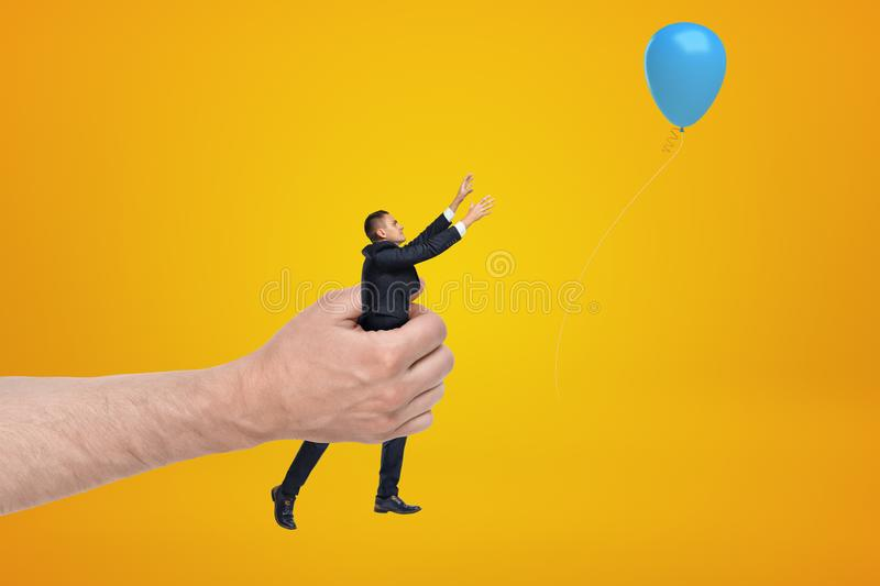 Big male hand holding tiny businessman who is reaching to blue balloon on yellow background stock images