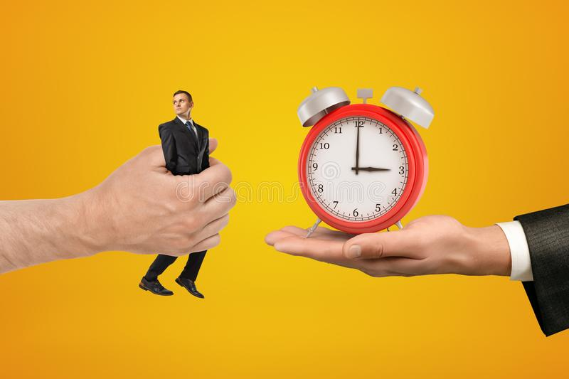 Big male hand passing tiny businessman to another hand with alarm clock on yellow background. Management and marketing. People and objects. Time and money stock image