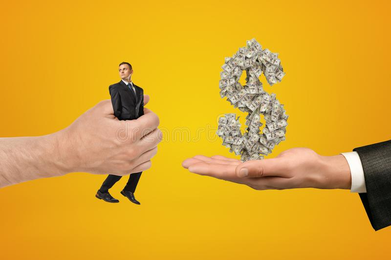 Big male hand passing tiny businessman to another hand with big money dollar sign on yellow background royalty free stock image