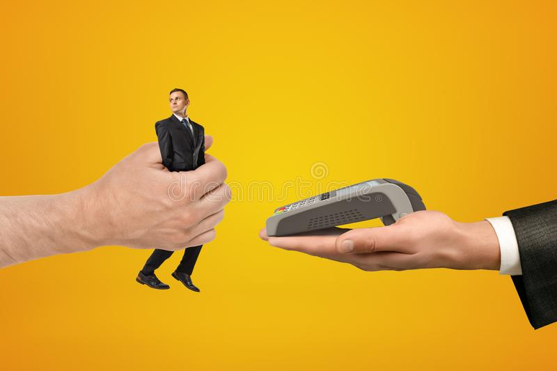 Big male hand passing tiny businessman to another hand with PIN pad on yellow background stock photo