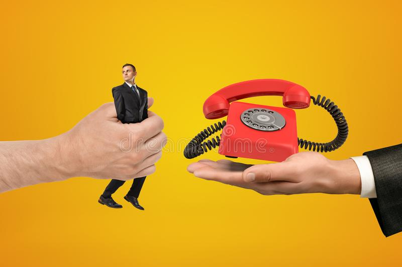 Big male hand passing tiny businessman to another hand with retro red telephone on yellow background. Management and marketing. People and objects. Telephone royalty free stock photo
