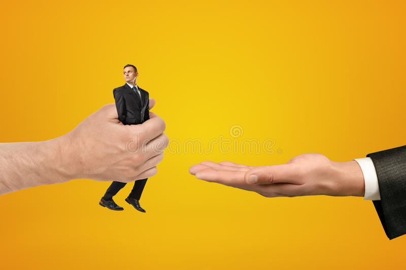 Big male hand passing tiny businessman to another hand on yellow background stock images