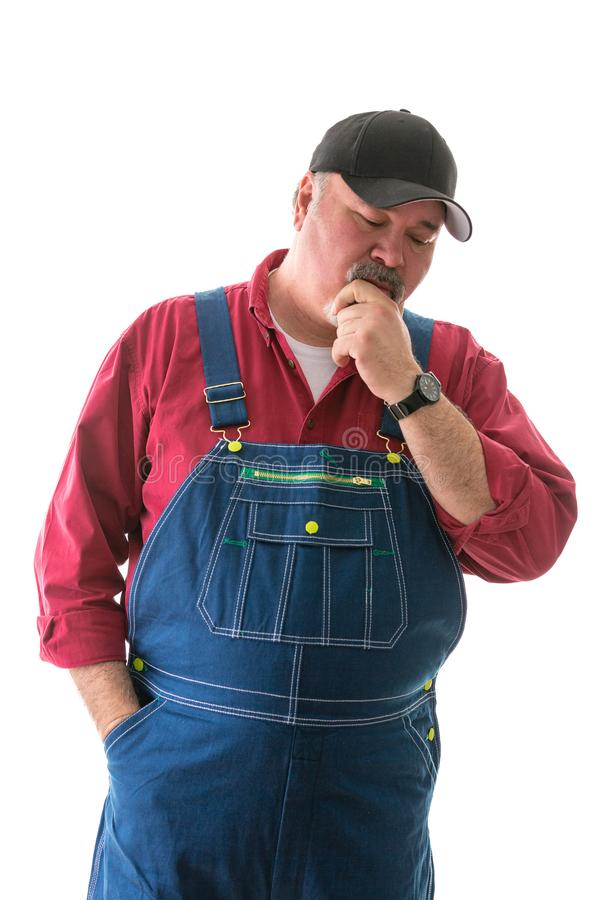 Big man in overalls and cap standing thinking stock images