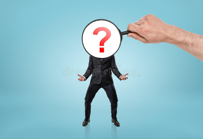 Big man's hand holding magnifying glass in front of question mark-headed businessman stock photo
