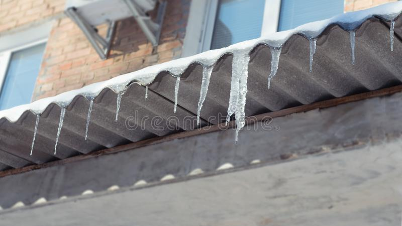 Big melting Icicles hang from roof of building. Danger for passers, threat of death and injury from icicles. Winter threats royalty free stock photography