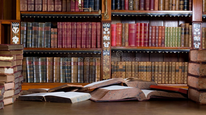 Big mess on the desk. Mess in studying room. Many vintage books in desk royalty free stock photography