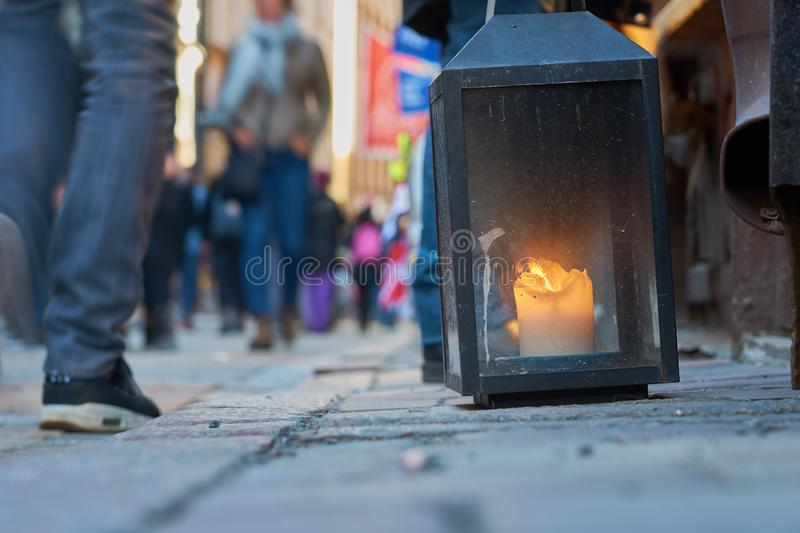 Big metal dirty lantern with burning candle inside, outdoor on a ground with blurred crowded street on a background. Copy space royalty free stock images