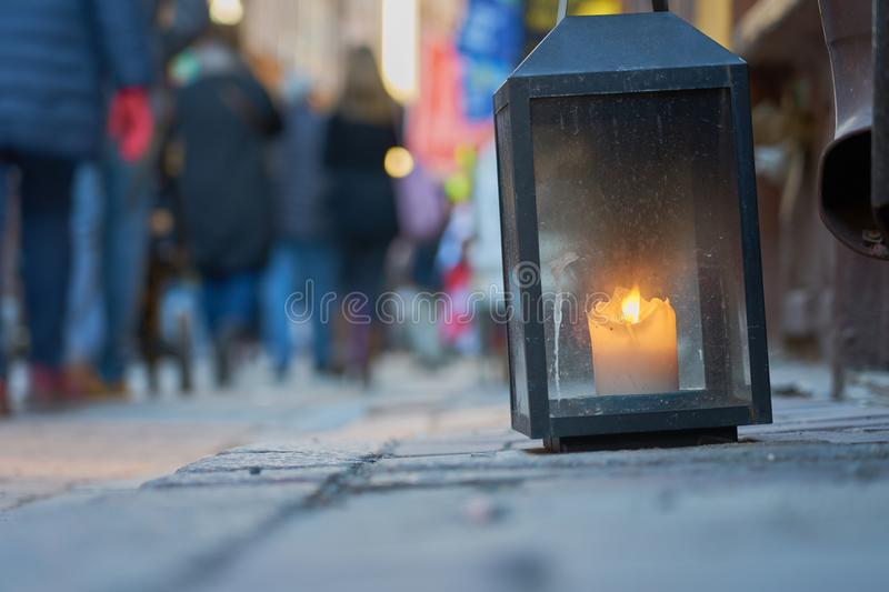 Big metal dirty lantern with burning candle inside, outdoor on a ground with blurred crowded street on a background. Copy space royalty free stock image