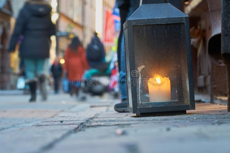 Big metal dirty lantern with burning candle inside, outdoor on a ground with blurred crowded street on a background. Copy space stock image