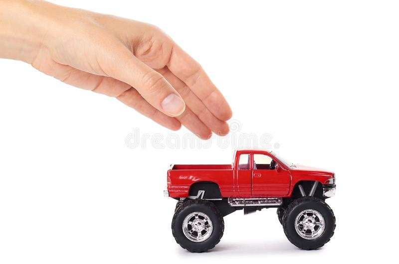 Big metal red toy car offroad with monster wheels in hand isolated on white background.  royalty free stock photography