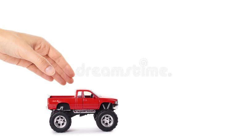 big metal red toy car offroad with monster wheels in hand isolated on white background. copy space, template royalty free stock photo