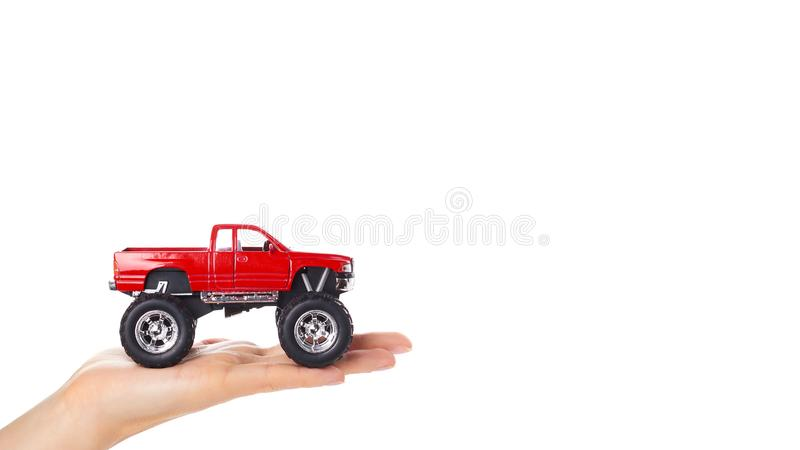 big metal red toy car offroad with monster wheels in hand isolated on white background. copy space, template stock photo