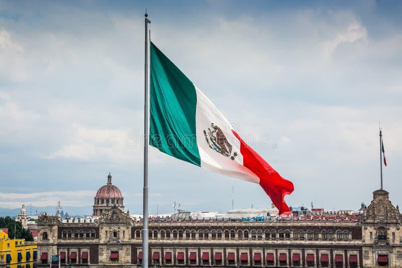 Big Mexican flag in main square Zocalo. With Palacio Nacional in background stock photo