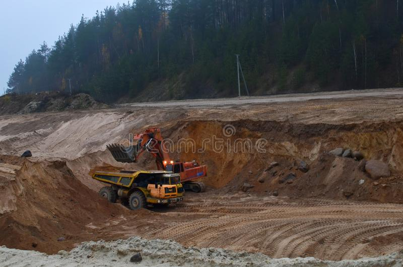 The big Mining dump truck is mining machinery, or mining equipment to transport sand from open-pit. Excavator loading of sand, ore royalty free stock image