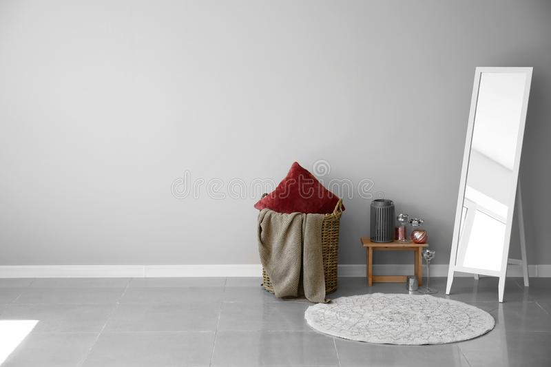 Big mirror, basket and decor near light wall royalty free stock photography