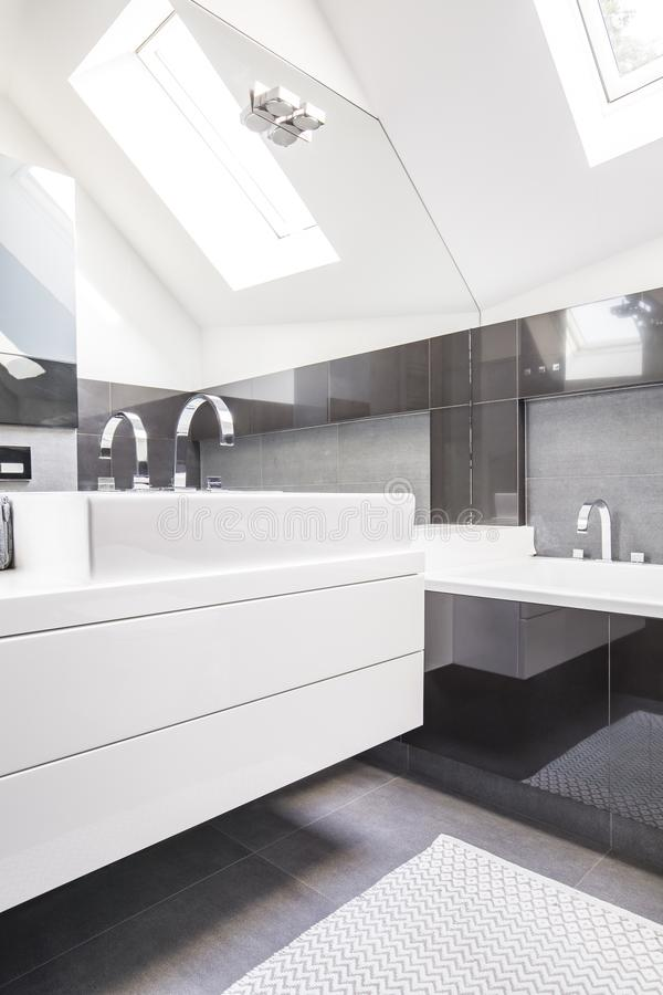 Big mirror by a modern, white washbasin cabinet in a fancy bathroom interior with reflective, black tiles and a roof window royalty free stock photos