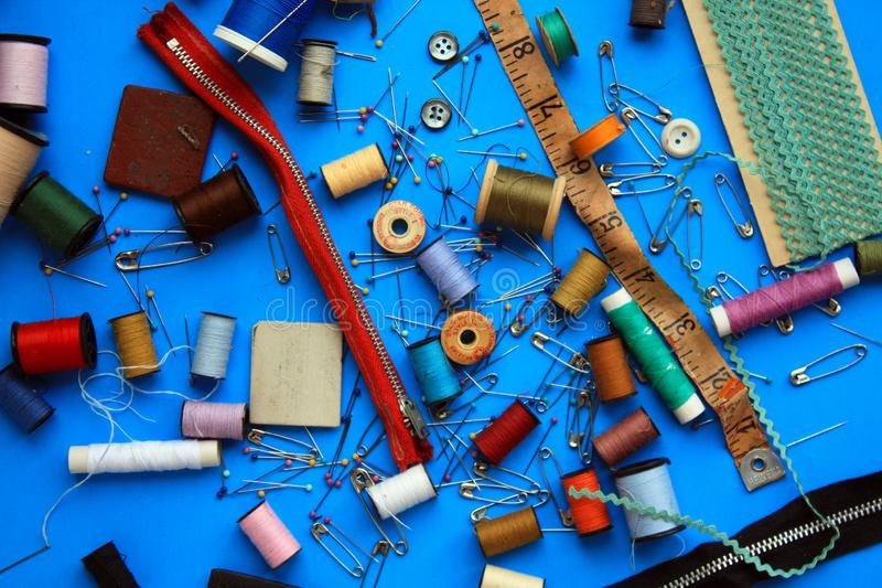 Big Mix of sewing pins and thread and sewing material. Big mix of sewing pins and safety pins different spools of thread. Measuring tape and red zipper. Buttons royalty free stock images