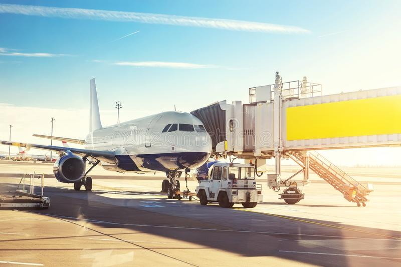 Big modern commercial plane on airfield docked with boarding bridge at sunrise or sunset. Blue clear sky on background. Travel and. Tourist destination concept royalty free stock images