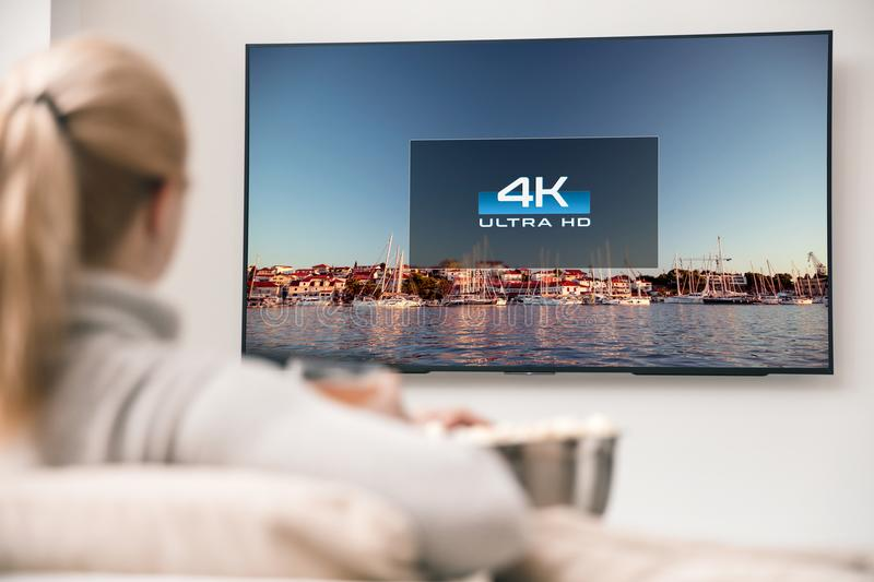 Big modern TV with 4k resolutions. And young woman on foreground watching some video stock image