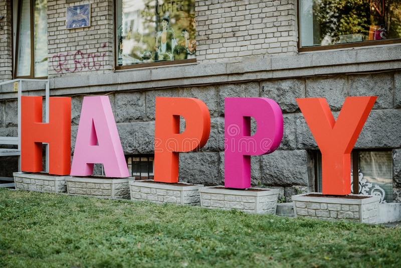 Big multi-colored letters HAPPY on city street, street art installation. Kiev, Ukraine - September 02, 2019. Word, tower, design, editorial, landmark, love royalty free stock image
