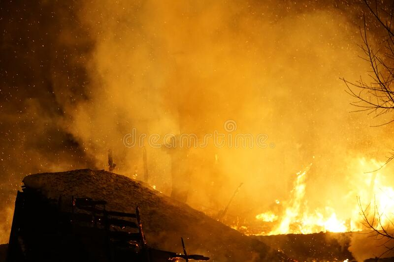Big night fire, catastrophe in Australia. Big fire, orange flame at night on a black background, charred wooden house, sparks, catastrophe, fires in Australia stock photo