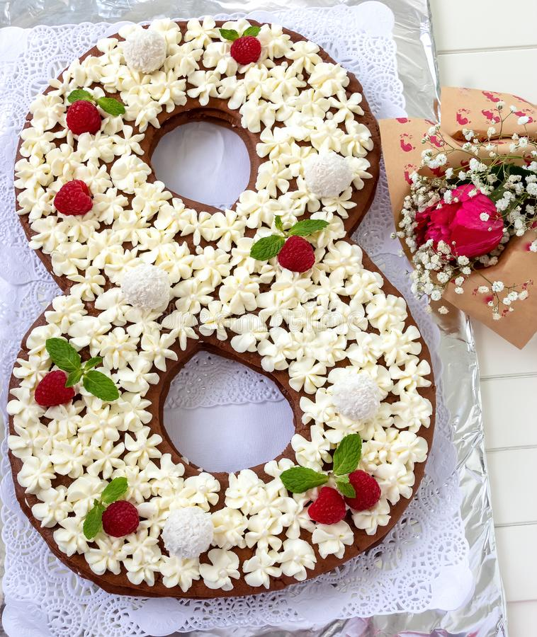 Big number cake and red rose flower. Cake shape of number 8 decorated white creamcheese, raspberry and coconut candy. stock photos