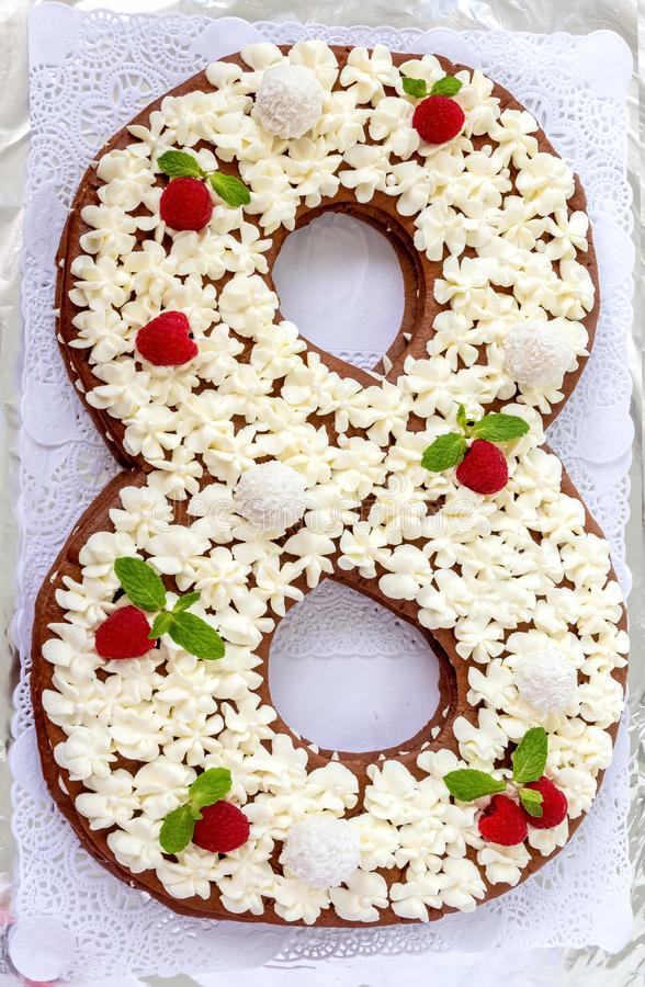 Big number cake and red rose flower. Cake shape of number 8 decorated white creamcheese, raspberry and coconut candy. royalty free stock images