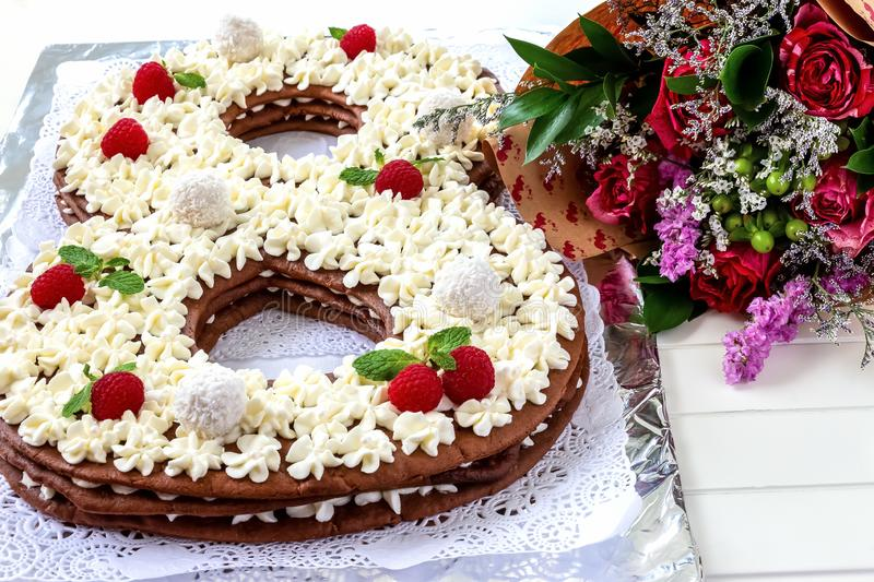 Big number cake and red rose flower. Cake shape of number 8 decorated white creamcheese, raspberry and coconut candy. royalty free stock image