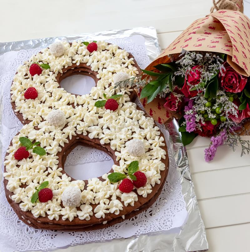 Big number cake and red rose flower. Cake shape of number 8 decorated white creamcheese, raspberry and coconut candy. stock photography
