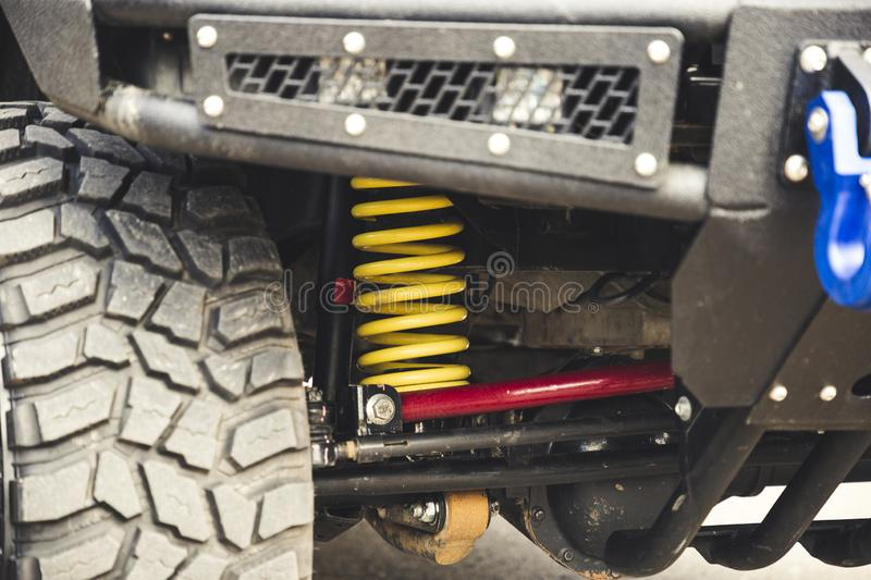 Big off road car coil spring. Yellow shock absorber on the car. Big off road car coil spring. Yellow shock absorber on the car stock image