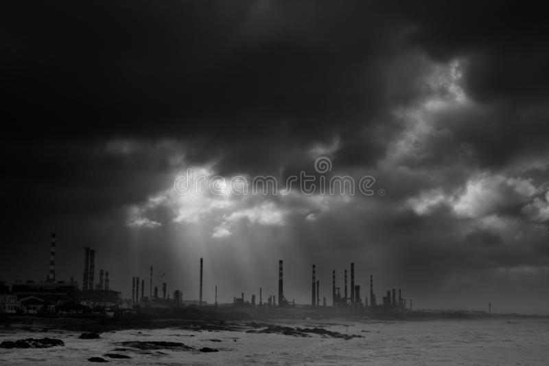 Oil refinery before storm. Big oil refinery by the sea against dramatic sky before heavy storm. Converted black and white royalty free stock image