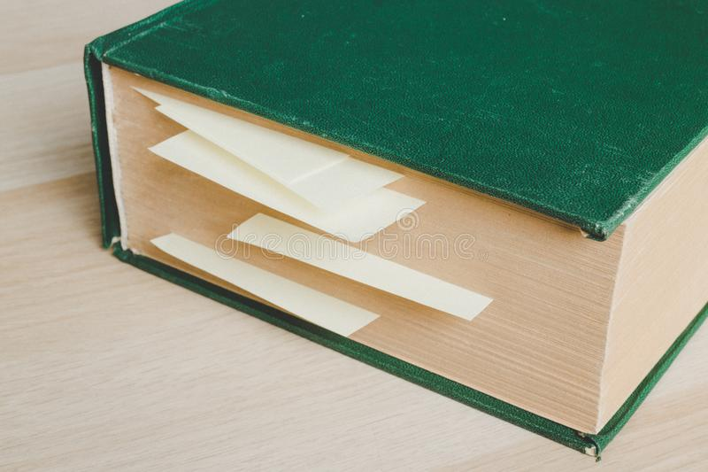 Big old book with tag pages by yellow sticky notes stock photo
