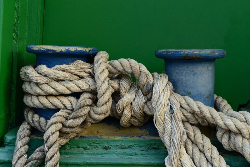 A big old cleat with classic mooring rope tied on it stock photo