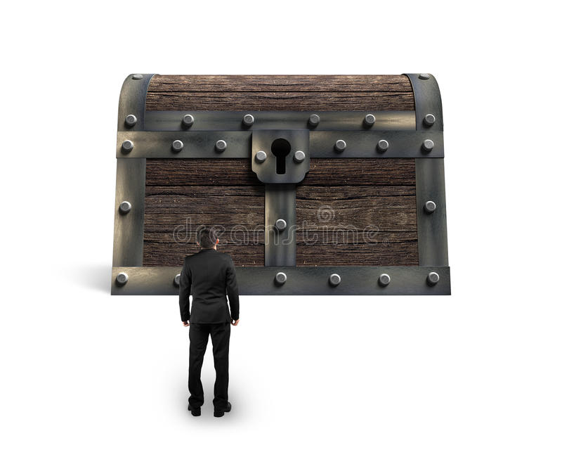 Big old treasure chest with small businessman looking at stock images