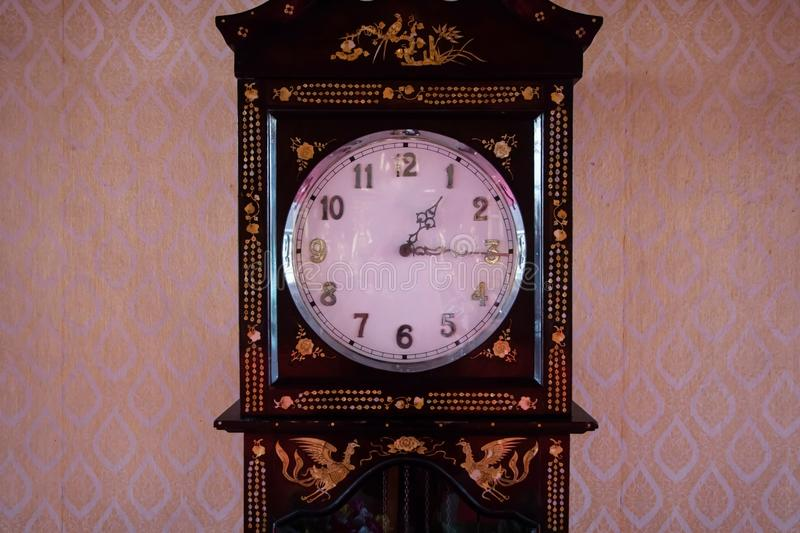 Big old vintage pendulum clock with thai pattern background at a. Ncient temple stock photo