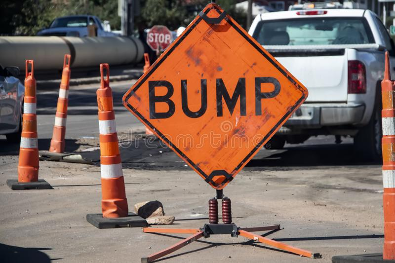 Big orange grungy sign that says BUMP surrounded by highway construction cones with trucks and torn up pavement in the background stock image
