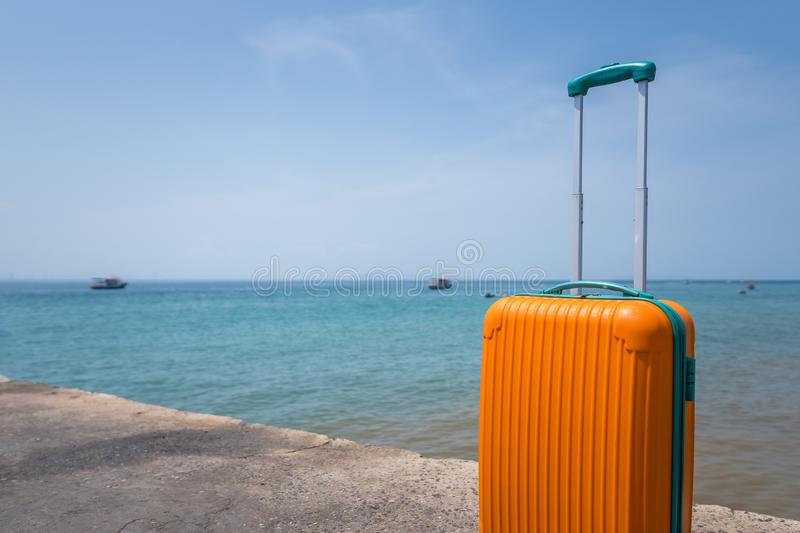 Big orange suitcase on the ocean beach background royalty free stock images