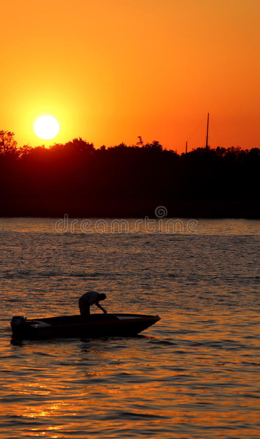 Big orange sun at sunset and the boat of fisherman. Big orange sun at sunset and the fisherman`s boat in the middle of the sea royalty free stock photo