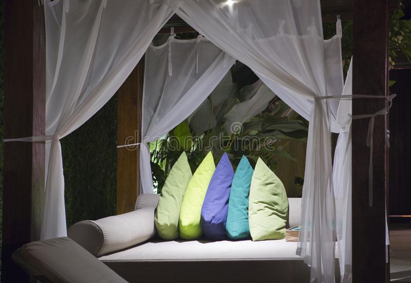 Big outdoor bed under bed curtains with bright color pillows royalty free stock photos
