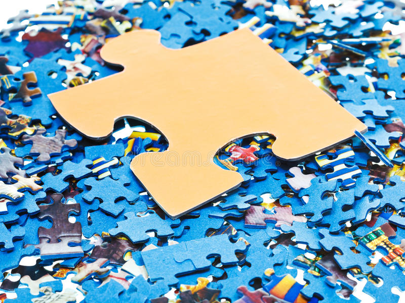 Big piece on pile of disassembled puzzles. One big piece on pile of disassembled little blue jigsaw puzzles stock image