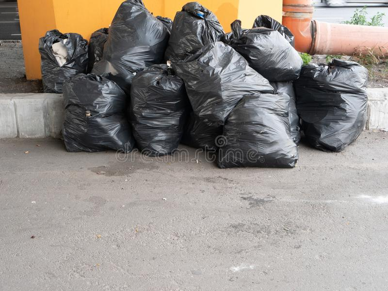 Big pile of black plastic garbage trash bags. Stacked on the street. depict utility workers strike royalty free stock photos