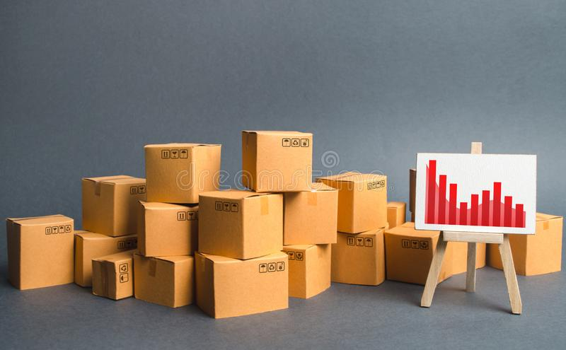 A big pile of cardboard boxes and a stand with information chart. Increasing consumer demand, exports or imports. rate growth. Of production of goods and royalty free stock photo
